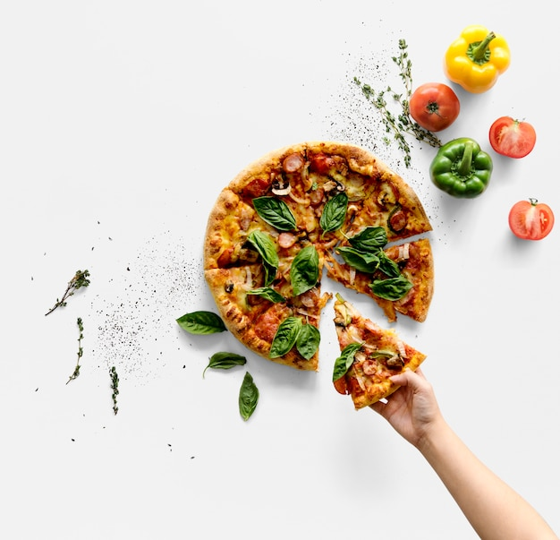Рука, взяв кусочек итальянской кухни пиццы