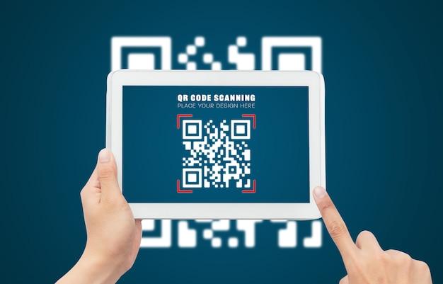 Рука с помощью планшетного компьютера сканирует qr-код макет