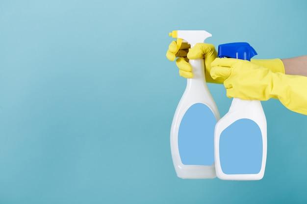 Hand in yellow glove holds spray bottle of liquid detergent.