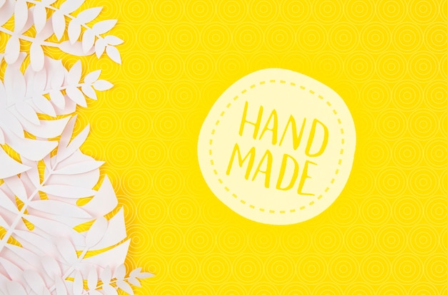 Handmade badge with white leaves on yellow background