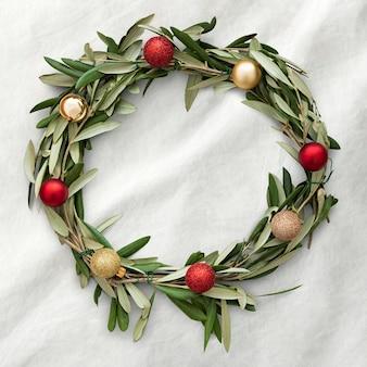 白い布の背景に手作りのクリスマスリースの装飾