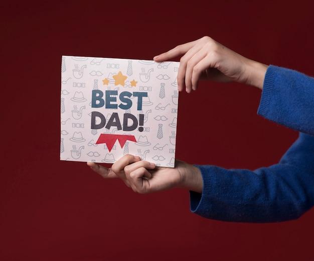 Руки держат картонный макет на бордовом фоне