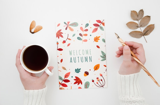 Hands holding coffee and pen next to autumn card