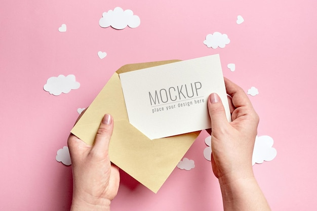 Hands holding greeting card mockup with paper clouds and hearts on pink