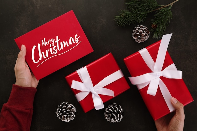 Hands holding merry christmas greeting card mockup template and gift box with christmas gifts decorations.