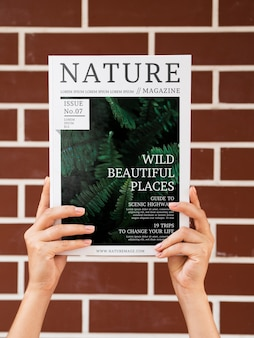 Hands holding a nature magazine mock up