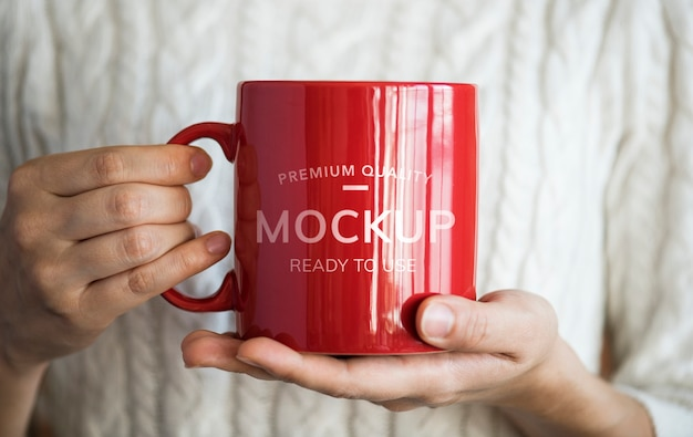 Hands holding a red mockup mug