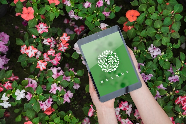 Hands holding tablet mockup with gardening concept