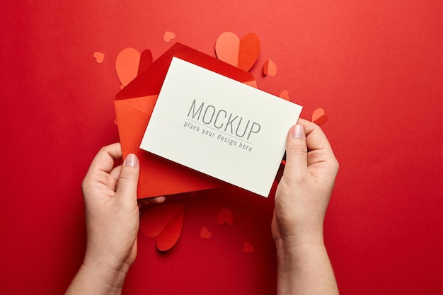 Hands holding valentines day card mockup with envelope and paper hearts on red