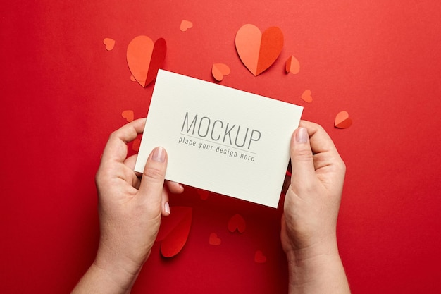 Hands holding valentines day card mockup with paper hearts on red