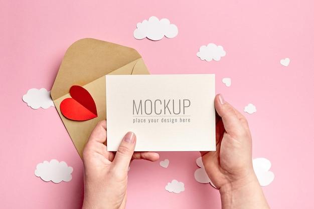 분홍색에 종이 구름과 하트와 valrntines 하루 카드 모형을 들고 손