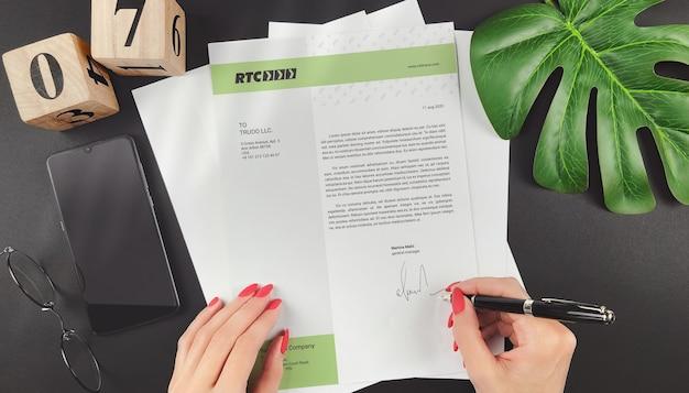法的文書のモックアップに署名する若いビジネス女性の手