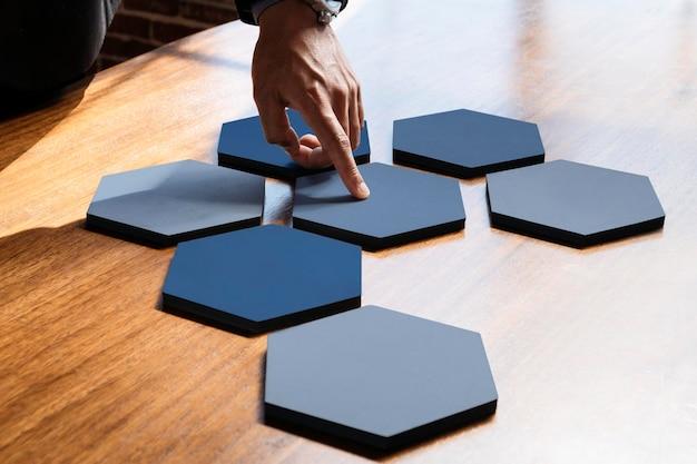 接続された六角形の切り抜かれた紙を指す手