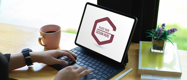 Руки печатают на клавиатуре планшета макета на деревянном столе