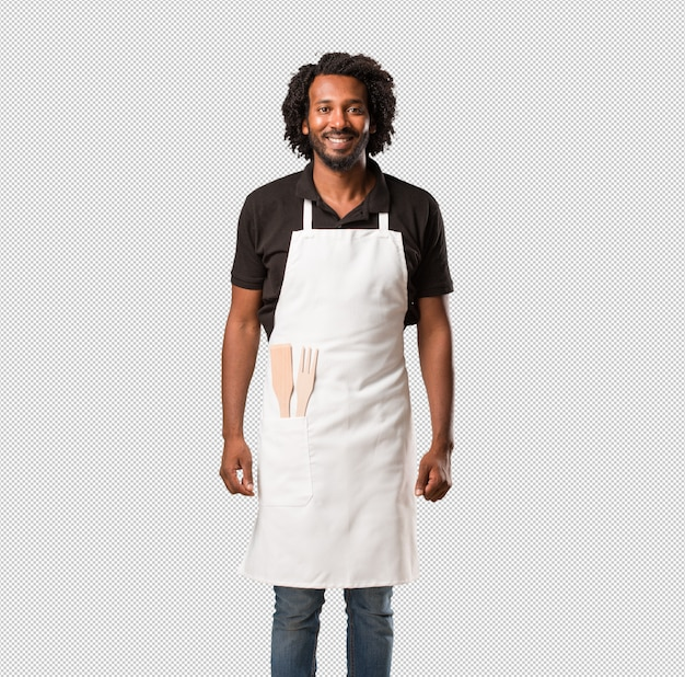 Handsome african american baker cheerful and with a big smile, confident, friendly and sincere, expressing positivity and success