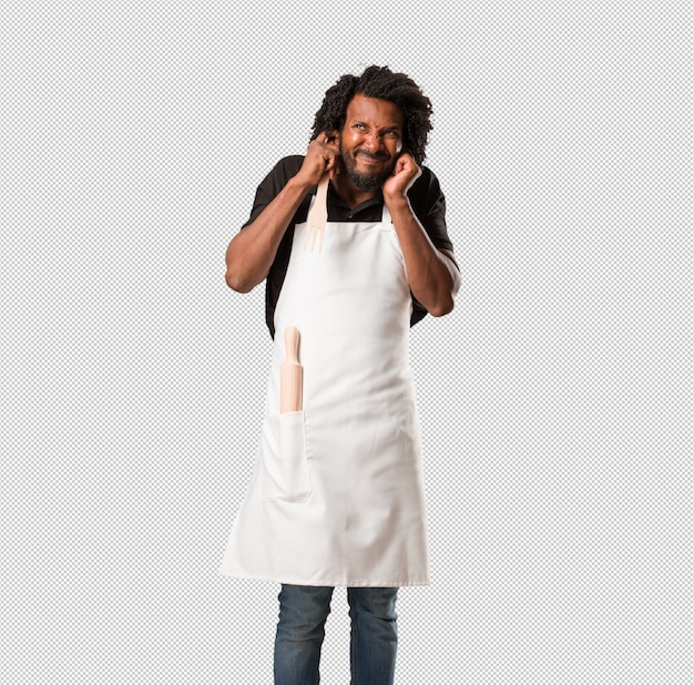 Красивый афро-американский пекарь, закрывающий уши руками, злой и усталый от слышания звука