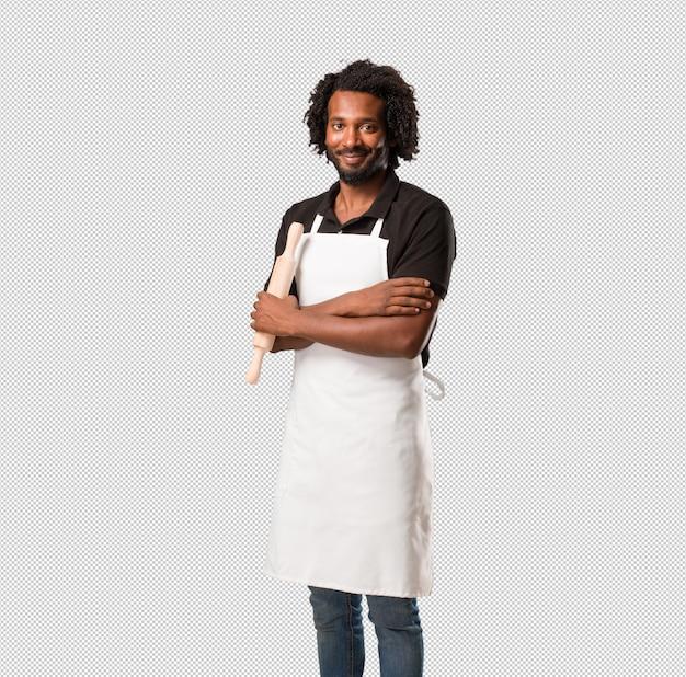 ハンサムなアフリカ系アメリカ人のパン屋彼の腕を組んで、笑顔と幸せ、自信を持ってフレンドリー