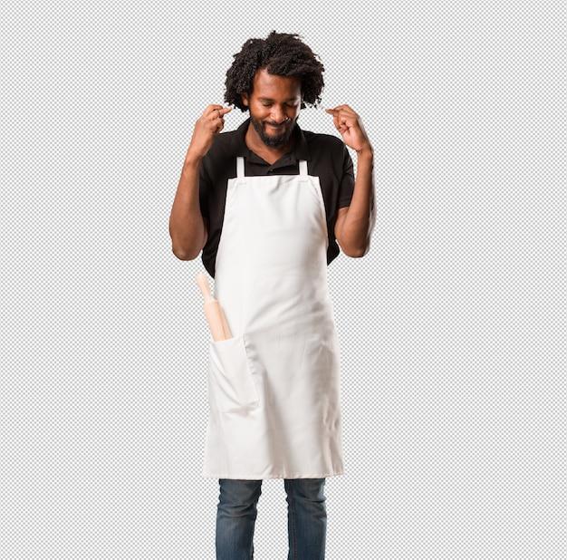 彼の指を交差するハンサムなアフリカ系アメリカ人のパン屋