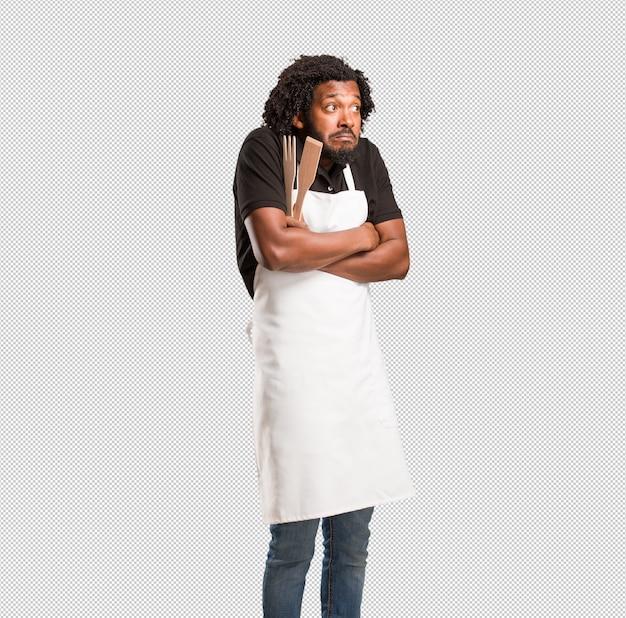 ハンサムなアフリカ系アメリカ人のパン屋は肩を疑い、肩をすくめ、優柔不断と不安の概念、何かについて不確か