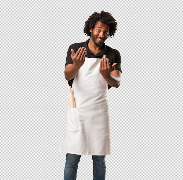 Handsome african american baker inviting to come, confident and smiling making a gesture with hand, being positive and friendly