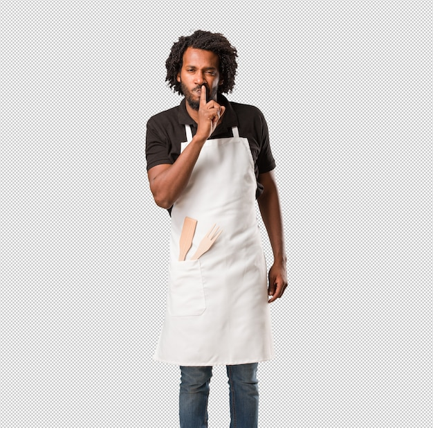 Handsome african american baker keeping a secret or asking for silence, serious face, obedience concept