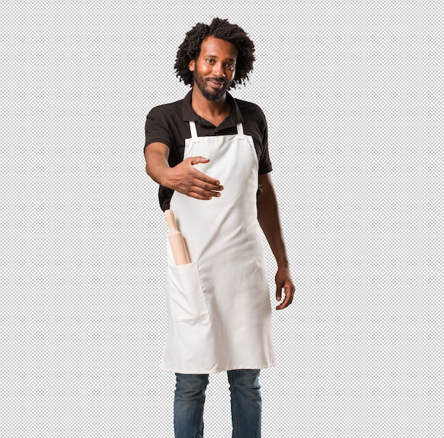 Handsome african american baker reaching out to greet someone or gesturing to help, happy and excited
