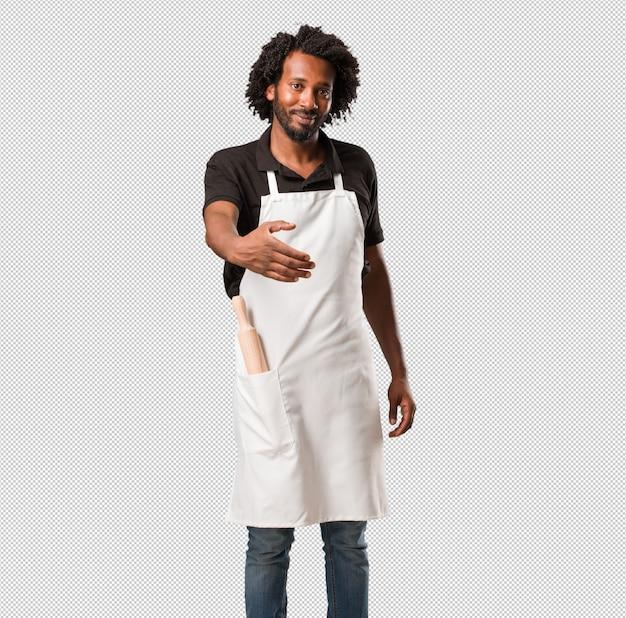 ハンサムなアフリカ系アメリカ人のパン屋が誰かに挨拶するために手を差し伸べる、または身振りで示す、幸せと興奮