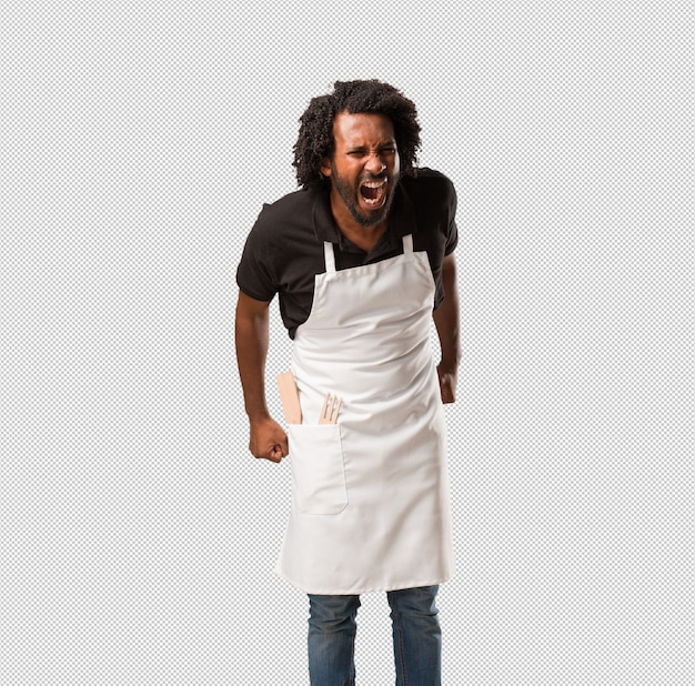 Handsome african american baker screaming angry, expression of madness and mental instability, open mouth and half-opened eyes, madness