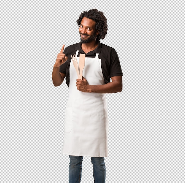 Handsome african american baker showing number one, symbol of counting,  mathematics, confident and cheerful