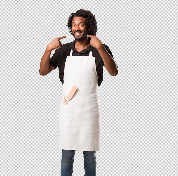 ハンサムなアフリカ系アメリカ人のパン屋の笑顔、ポインティング口、完璧な歯の概念、白い歯、陽気で陽気な態度