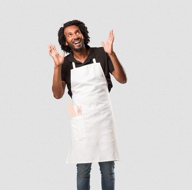 Handsome african american baker surprised and shocked, looking with wide eyes, excited by an offer or by a new job, win concept