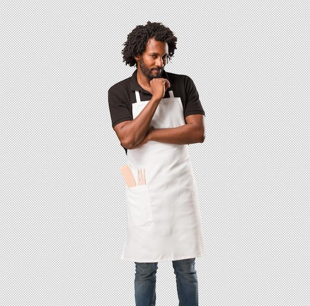 アイデアについて混乱して考えて見上げるハンサムなアフリカ系アメリカ人のパン屋は、解決策を見つけようとしている