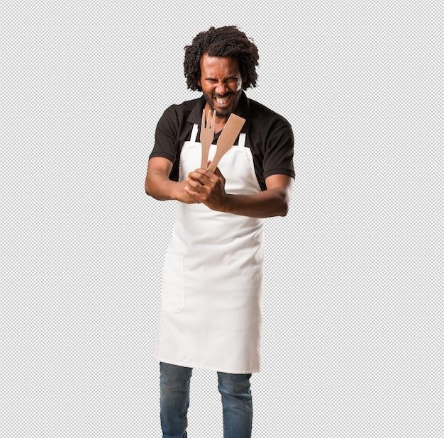 ハンサムなアフリカ系アメリカ人のパン屋は非常に怒って怒って、非常に緊張して、叫んで猛烈で、否定的でクレイジーです