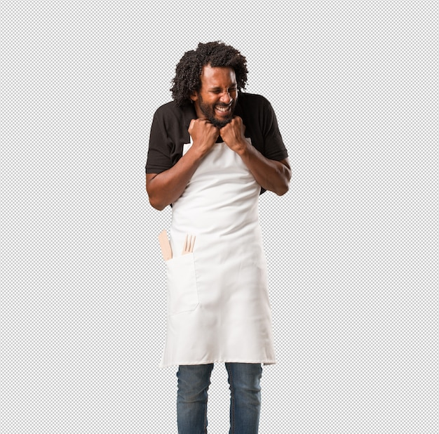 Handsome african american baker very happy and excited, raising arms, celebrating a victory or success, winning the lottery