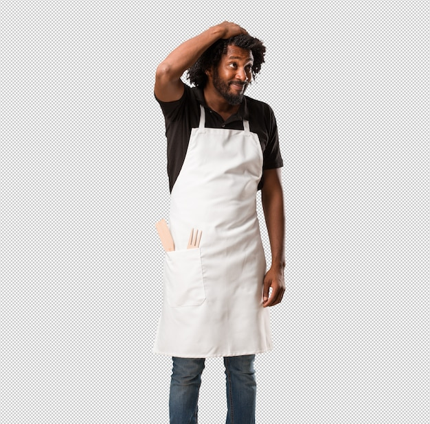 Handsome african american baker worried and overwhelmed, forgetful, realize something, expression of shock at having made a mistake