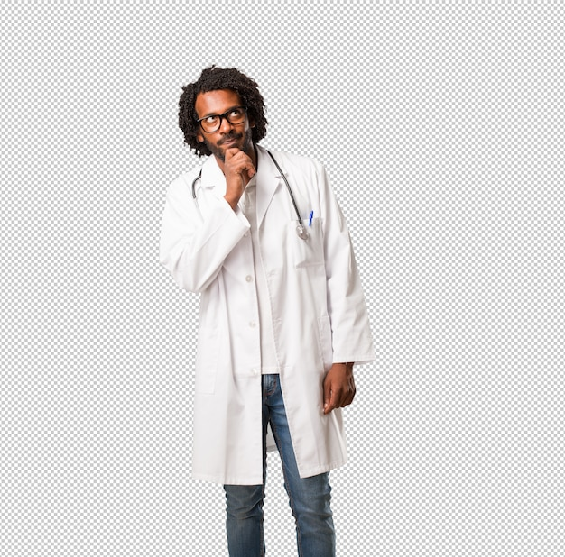 Handsome african american medical doctor doubting and confused, thinking of an idea or worried about something