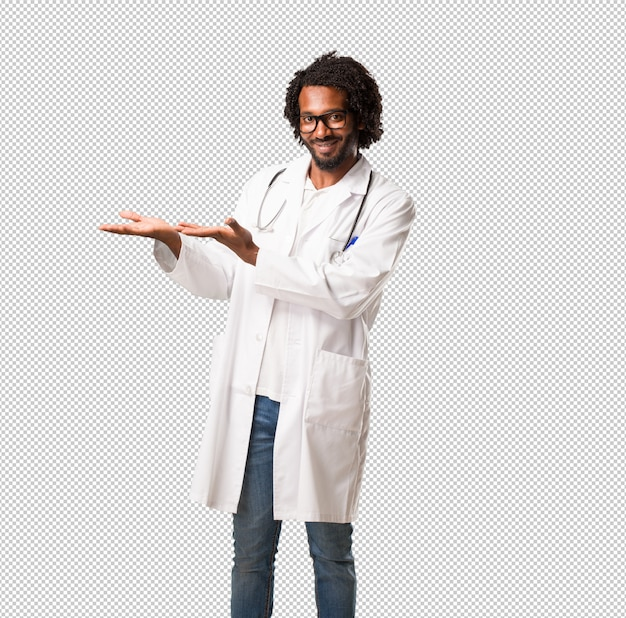 Handsome african american medical doctor holding something with hands, showing a product, smiling and cheerful, offering an imaginary object