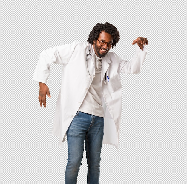 Handsome african american medical doctor listening to music, dancing and having fun, moving, shouting and expressing happiness, freedom