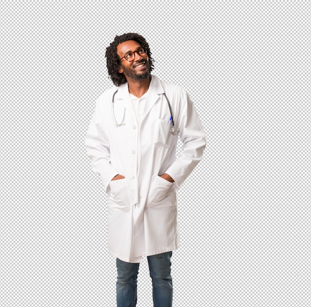 Handsome african american medical doctor looking up, thinking of something fun and having an idea,  imagination, happy and excited