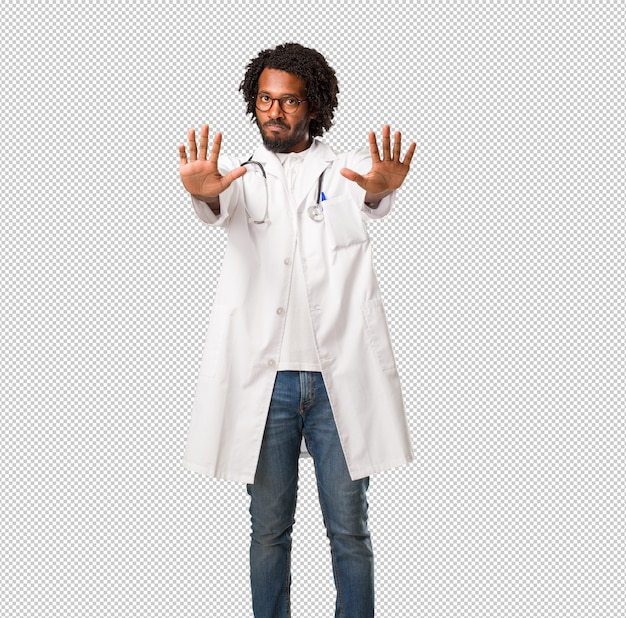 Handsome african american medical doctor serious and determined, putting hand in front, stop gesture, deny