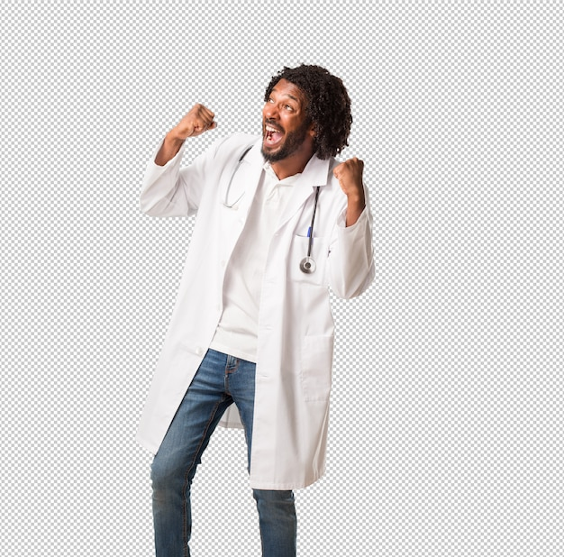 Handsome african american medical doctor very happy and excited, raising arms, celebrating a victory or success, winning the lottery