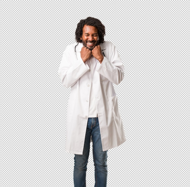 Handsome african american medical doctor very happy and excited, raising arms