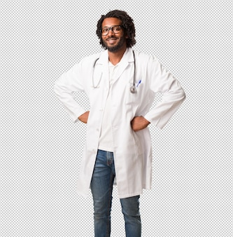 Handsome african american medical doctor with hands on hips, standing, relaxed and smiling, very positive and cheerful