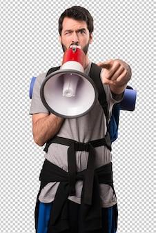 Handsome backpacker holding a megaphone