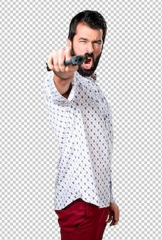 Handsome brunette man with beard holding a pistol