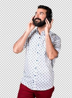 Handsome brunette man with beard listening music