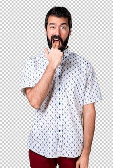 Handsome brunette man with beard making vomiting gesture