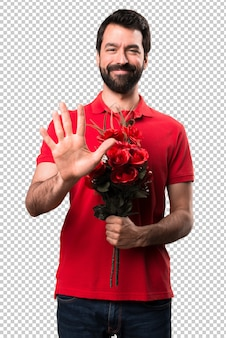 Handsome man holding flowers counting five