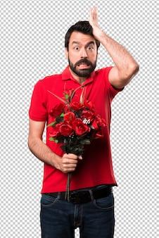Handsome man holding flowers having doubts
