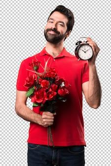 Handsome man holding flowers holding vintage clock